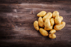 Fresh organic potatoes on a wooden table Stock Images