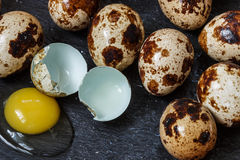 Fresh organic quail eggs whole and broken. On black Board Royalty Free Stock Photography