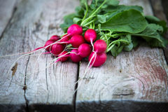 Fresh organic radish on a old wooden background. Radishes with tops Royalty Free Stock Photos