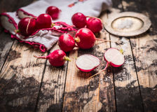 Fresh organic radish with salt on rustic kitchen table. Simple food Royalty Free Stock Images