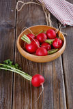 Fresh organic radish on a wooden bowl. On a rustic wooden background stock image