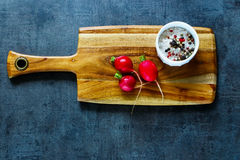 Fresh organic radish. Wooden cutting board with fresh organic radish and spices on dark vintage background, top view, place for text. Simple food concept Royalty Free Stock Photography