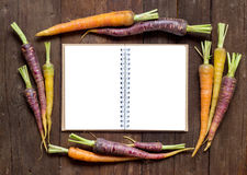 Fresh organic rainbow carrots with Recipes book Royalty Free Stock Photo