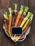 Fresh organic rainbow carrots and a small chalkboard Stock Image