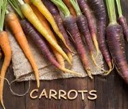Fresh organic rainbow carrots and word Carrots Stock Photo