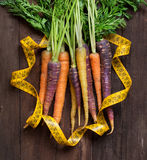 Fresh organic rainbow carrots and yellow measuring type Royalty Free Stock Photos