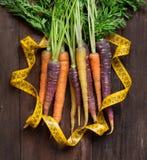 Fresh organic rainbow carrots and yellow measuring type Royalty Free Stock Photos