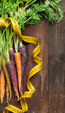 Fresh organic rainbow carrots and yellow measuring type Royalty Free Stock Images
