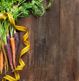 Fresh organic rainbow carrots and yellow measuring type Stock Image