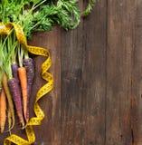 Fresh organic rainbow carrots and yellow measuring type Stock Image