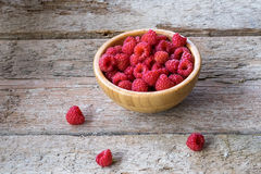 Fresh organic raspberries in bowl wood background. Stock Photography