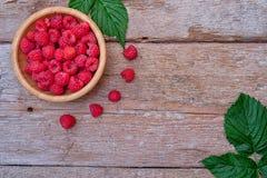 Fresh organic raspberries on bowl wood background. Top View. Organic raspberries on wood background. Top view Stock Image