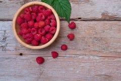 Fresh organic raspberries on bowl wood background. Top View. Organic raspberries on wood background. Top view Stock Photography