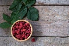 Fresh organic raspberries on bowl wood background. Top View Stock Photo