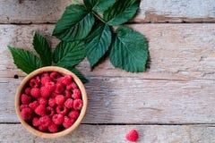 Fresh organic raspberries on bowl wood background. Top View. Organic raspberries in bowl with leaf. Wood background. Top view Royalty Free Stock Image