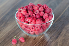 Fresh organic raspberries in glass bowl. On wooden table Stock Photo