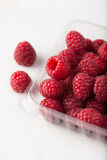 Fresh, organic raspberries in a plastic container over white bac. Kground, selective focus, close up, studio, vertical Royalty Free Stock Photos