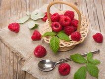 Fresh organic raspberry in basket. Fresh raspberries in a basket on rustic wooden background Stock Image
