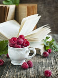 Fresh organic raspberry in cup. Fresh organic raspberry in cup on wooden table Royalty Free Stock Photos