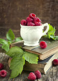 Fresh organic raspberry in cup. Fresh organic raspberry in cup on wooden table Stock Photography