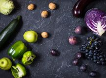 Fresh organic raw green and purple colored vegetables and fruits on dark stone background Royalty Free Stock Image