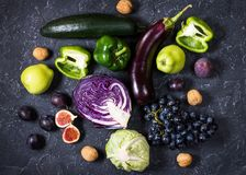 Fresh organic raw green and purple colored vegetables and fruits on dark stone background Royalty Free Stock Photo