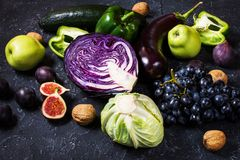Fresh organic raw green and purple colored vegetables and fruits on dark stone background Royalty Free Stock Images