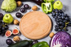 Fresh organic raw green and purple colored vegetables and fruits on stone background. Stock Photo