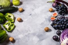 Fresh organic raw green and purple colored vegetables and fruits on stone background. Royalty Free Stock Images