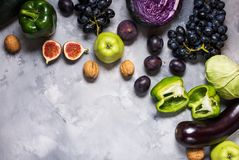 Fresh organic raw green and purple colored vegetables and fruits on stone background Stock Photography