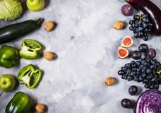 Fresh organic raw green and purple colored vegetables and fruits on stone background. Top view. Copyspace. Royalty Free Stock Image