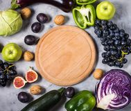 Fresh organic raw green and purple colored vegetables and fruits on stone background. Top view. Copyspace. Stock Photo