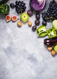 Fresh organic raw green and purple colored vegetables and fruits on stone background. Top view. Royalty Free Stock Photos