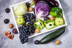 Fresh organic raw green and purple colored vegetables and fruits in white tray on dark stone background Stock Photo