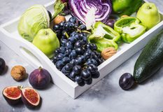 Fresh organic raw green and purple colored vegetables and fruits in white tray on dark stone background Stock Image