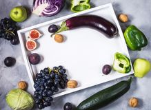 Fresh organic raw green and purple colored vegetables and fruits in white tray on stone background. Copyspace Royalty Free Stock Images