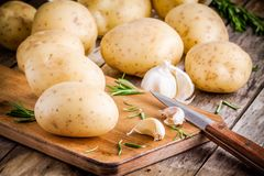 Fresh organic raw potatoes with rosemary and garlic on the old table Royalty Free Stock Images