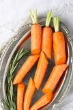 Fresh organic raw sliced carrots with rosemary on metal plate Royalty Free Stock Photography