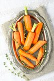 Fresh organic raw sliced carrots with thyme on metal plate.  Stock Photos