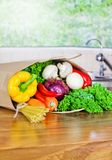 Fresh Organic Raw Vegetables food delivery in paper bag on wooden bench stock photo