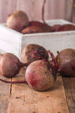 Fresh organic red beets. In a wooden box on rustic background Royalty Free Stock Photos