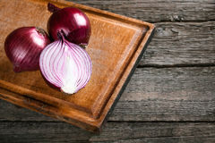 Fresh organic red onions. On a wooden background royalty free stock photos