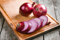Fresh organic red onions. On a wooden background Stock Photos