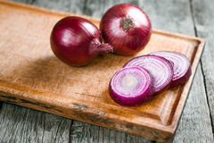 Fresh organic red onions. On a wooden background royalty free stock photo