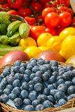 Fresh organic ripe blueberries in a basket and various fruits and vegetables. Fresh organic ripe blueberries in a basket with other blurred out of focus fruits stock images