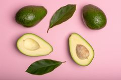 Fresh organic ripe green whole and sliced Fuerte avocado with le. Aves, copy space close up  on trendy pink background Stock Images