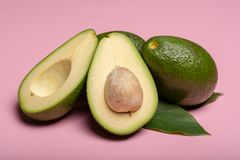 Fresh organic ripe green whole and sliced Fuerte avocado with le. Aves, copy space close up  on trendy pink background Stock Photography