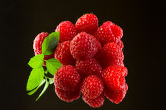 Fresh organic ripe raspberries on black background. Stack of fresh, delicious, organic, ripe raspberries, green leaves on black background. Excellent source of Royalty Free Stock Image