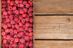 Fresh organic ripe raspberry in box. On wooden table with copy space Royalty Free Stock Photo