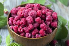 Fresh organic ripe raspberry with leaf in bowl on wooden table. Selective focus Stock Photos